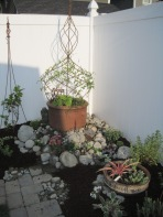 "Getting the ""bones"" of a pocket garden right are the key to beautiful growth. Here, containers and supports are combined with a surrounding rock garden."